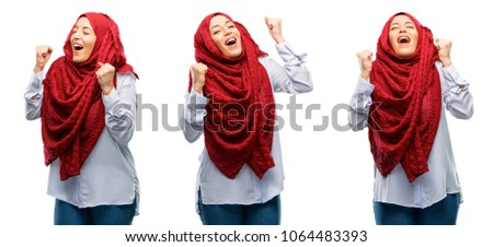 Arab woman wearing hijab happy and excited expressing winning gesture. Successful and celebrating victory, triumphant isolated over white background
