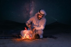 Arab young man sitting around bonfire in the desert, Arabic comping, middle east tourism concept.