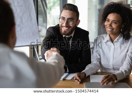 Arabian and african HR manager greeting applicant starting job interview, middle eastern ethnicity and american company representatives welcoming corporate client shake hands sitting at desk in office