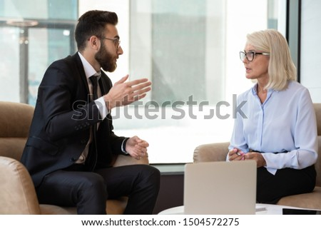 Arabian and caucasian business partners different generation businesspeople meet in office seated on armchairs discuss deal startup ideas, hr manager and applicant during job interview process concept