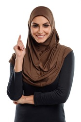 Arabian business woman got an idea. Elegant woman with wide smile points her finger up, isolated on white.