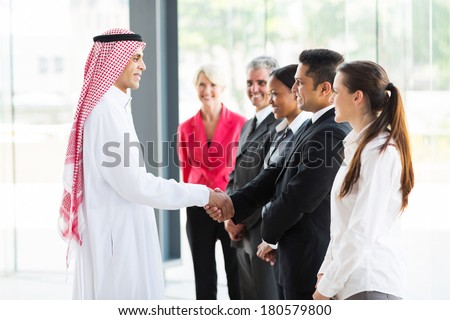arabian businessman handshaking with group of his employees in office