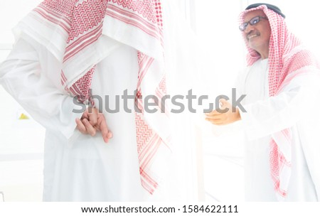 Arabian businessman in glasses wearing hijab shake hands together and holding another fingers crossed behind his back,Honesty isn't always,Dishonest businessman telling lies,Trickery Concept.