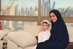 Arabian family, mother and son sitting on the couch in their living room