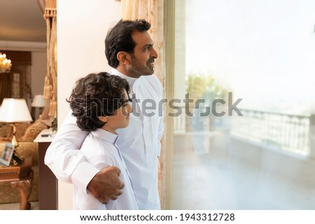 Arabian father embracing son at home  looking at the window