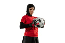 Arabian female soccer or football player, goalkeeper on white studio background. Young woman posing confident with ball, protecting goals for team. Concept of sport, hobby, healthy lifestyle.