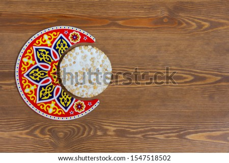 Arabian Islamic Background - Arabian Crescent with Islamic Texture with a piece of Halawet Al Mawlid Al Nabawi - Traditional candy - Egyptian Culture Dessert