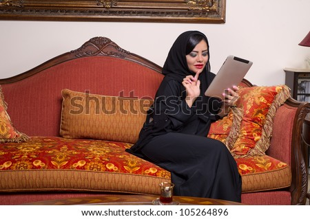 arabian lady with hijab using Pad at home