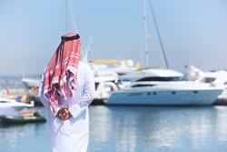 Arabian man looking at the yacht harbor, back view
