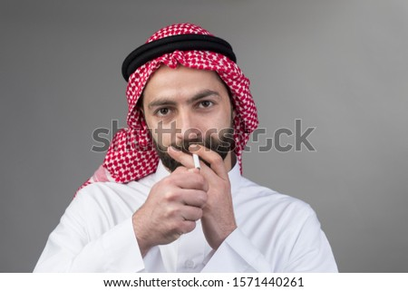 Arabian man smoking, Arabian man wearing traditional clothes and holding a cigarette