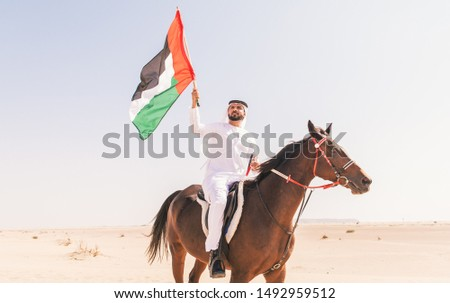 Arabian man with traditional clothes riding his horse