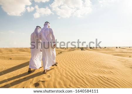 Arabian men witk kandora walking in the desert - Portrait of two middle eastern adults with traditional arabic dress