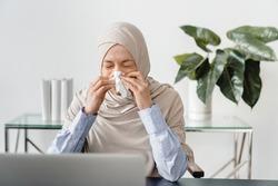 Arabian muslim mature businesswoman in hijab sneezing at home office. Sick ill female freelancer feeling unwell at workplace. Sick leave, allergy, respiratory illness, coronavirus concept