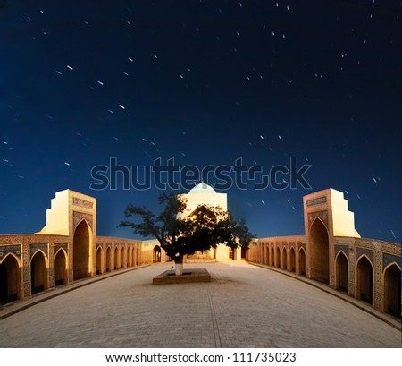 Arabian night. Night sky with star trails above Kolon mosque in Bukhara, Uzbekistan.