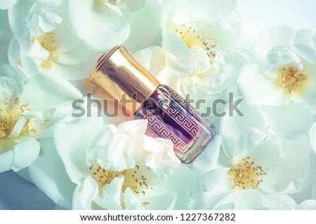 Arabian oud attar perfume or agarwood oil fragrances in mini bottle on the white flowers.  #1227367282
