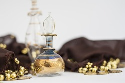 Arabian parfum bottles and brown belly dance belt with golden coin. Blurred photography, selective focus on glass decorations.