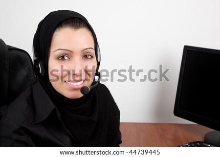 Arabic beautiful young woman with headphones with microphone in the office - stock photo