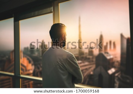 Arabic business man looking out through the office balcony seen through glass window. arab young man looking at Dubai city through hotel window. Foto stock ©