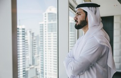 Arabic businessman looking out the window in his office
