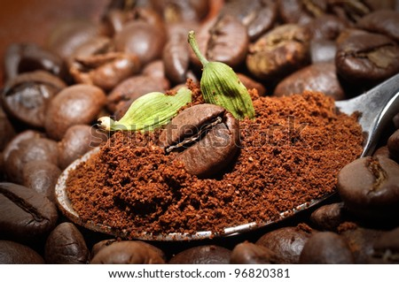 Arabic coffee beans with green cardamom - traditional oriental drink. Closeup of coffee bean at roasted coffee heap.
