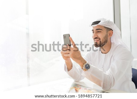 Arabic corporate business man wearing kandora looking at mobile phone and smiling - Portrait of traditional Emirati man Foto d'archivio ©