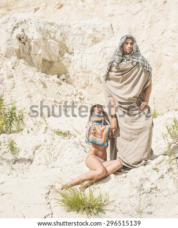 Arabic Couple muslim Looking at camera Arab man and woman in white sand desert against dry desert Empty space for inscription Young rich family