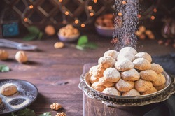 Arabic Cuisine; Delicious cookies for celebration of El-Fitr Islamic Feast( The Feast that comes after Ramadan). Sprinkling powdered sugar on Kahk(Eid Al-Fitr cookies).