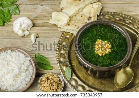 Arabic cuisine:Egyptian dish molokhya or mulukhiya placed with white rice, fresh traditional bread and crispy fried garlic on rustic wooden background.