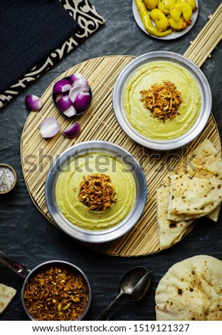 Arabic cuisine, Egyptian fava beans and herbs dip ( Bessara). It contains fava beans, onion, garlic and fresh herbs. Served with crispy fried onions,bread,pickles and fresh onios.