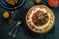 Arabic cuisine, Egyptian oriental Fettah with white rice and crispy bread topped with seasoned garlic red sauce,crispy fried garlic and veal chunks on rustic dark background.Top view,close-up