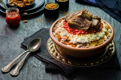 Arabic cuisine, Egyptian oriental Fettah with white rice and crispy bread topped with seasoned garlic red sauce,crispy fried garlic and veal chunks on rustic dark background.