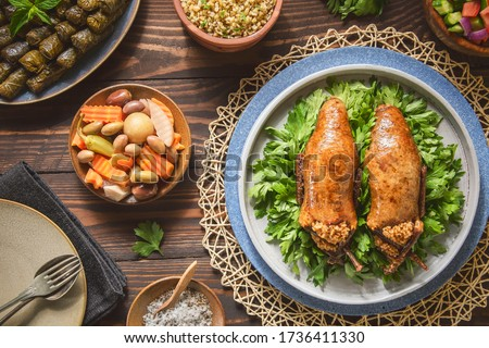 Arabic Cuisine; Egyptian traditional stuffed pigeon or 'Hamam Mahshi' dish. Served with green salad, oriental pickles, cooked Freekeh and stuffed vine leaves. Close up with copy space. Stock photo ©