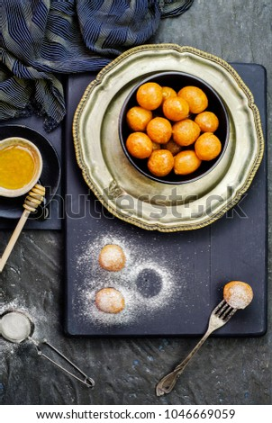 Arabic Cuisine; Middle Eastern dessert/Ramadan dessert Zalabya, or luqmat Al- Kadi served with honey and sugar on dark background