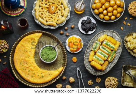 Arabic Cuisine:Middle Eastern desserts. Delicious collection of Ramadan traditional desserts. Served with tasty nuts, dried fruits,honey syrup and oriental tea.Top view with close up.