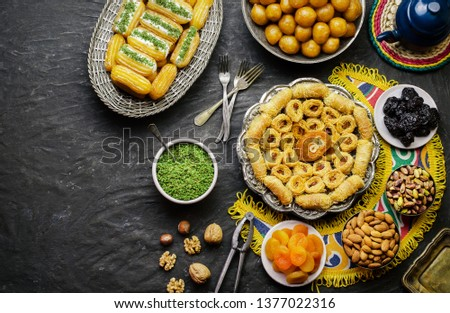 Arabic Cuisine:Middle Eastern desserts. Delicious collection of Ramadan traditional desserts. Served with tasty nuts, dried fruits,honey syrup and oriental tea.Top view with copy space. #1377022316