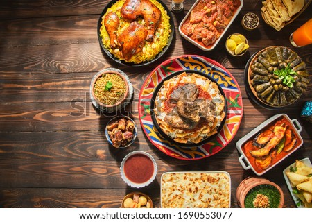 "Arabic Cuisine: Middle Eastern traditional lunch. It;s also Ramadan ""Iftar"" . The Meal eaten by Muslims after sunset during Ramadan. Assorted of Egyptian oriental dishes. Top view with copy space."