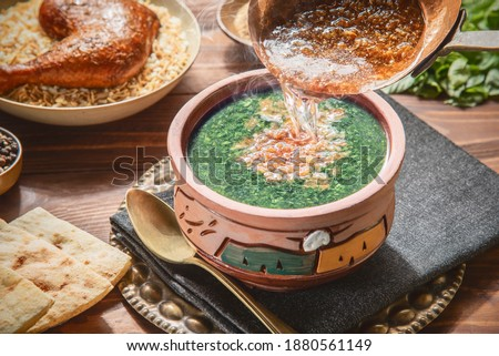 Arabic cuisine: Pouring fried golden garlic over a delicious stewed Molokhya . Traditional Egyptian meal served with rice, chicken, and pita bread on rustic wooden background. Photo stock ©