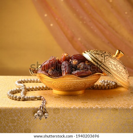Arabic dates in a decorative golden bowl with prayer beads. Ramadan or Ramzan objects and background Image.