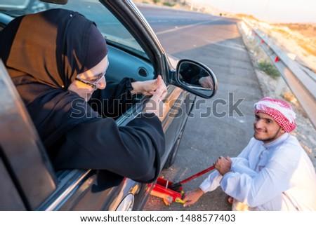 Arabic fixing his car flat tire