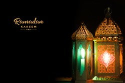 Arabic lantern glowing on a dark background. Ramadan concept image. Free space for your text.