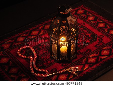 Arabic lantern on red carpet with wooden rosary - stock photo