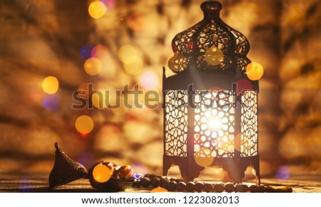Arabic lantern with candle at night for Islamic holiday. Muslim holy month Ramadan. The end of Eid and Happy New Year. Copy space on dark background. #1223082013