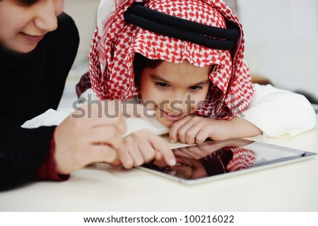 Arabic little boy and his mother working with touch tablet