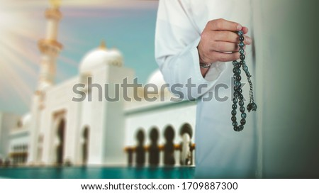 Arabic man hand holding a muslim rosary standing front a mosque. ramadan holy month, Ramadhan kareem concept.