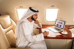 Arabic man wearing kandora in emirates style flying on exclusive private jet - Middle-eastern businessman with traditional dress flies in exclusive business class on airplane