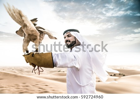 Arabic man with traditional emirates clothes walking in the desert with his falcon bird