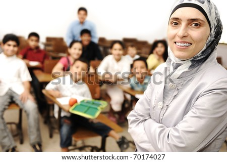 arabic Muslim kids in the school, classroom with a female smiling teacher - stock photo