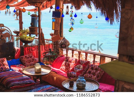 Arabic oriental cafe or hookah with trestle beds and colorful pillows on the sea coast #1186552873