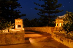 Arabic stone lanterns illuminate the path outside the hotel. Night landscape near the hotel in the middle East. Late night in Tunisia and the Arab clay lamp ornament