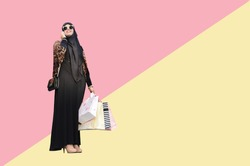Arabic woman holding a shopping bag on pink and yellow background, Shopping concept